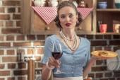 Fotografie schöne Erwachsene Hausfrau mit Glas Rotwein und frisch gebackenem Kuchen, Blick in die Kamera in Küche