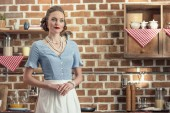 smiling adult housewife in vintage clothes standing at kitchen and looking away