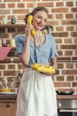 Fotografie beautiful happy housewife talking by vintage rotary phone at kitchen