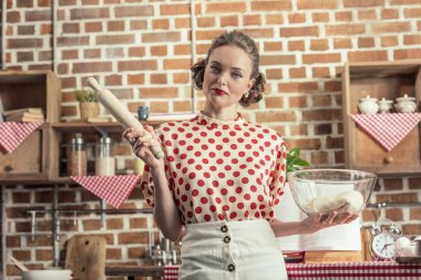 beautiful adult housewife with bowl of dough and rolling pin looking at camera at kitchen