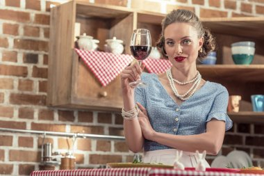 beautiful adult housewife with glass of red wine looking at camera at kitchen