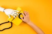oříznuté záběr ženy a robot sáhl po vinobraní telefon na žluté