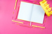 Photo top view of blank opened notebook with appliances and paper crown on pink