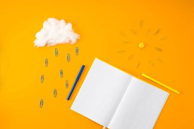 top view of blank notebook and cloud with sun made of paper clips and cotton on yellow