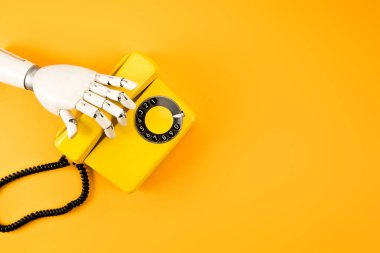 cropped shot of robotic hand reaching for vintage phone on yellow tabletop