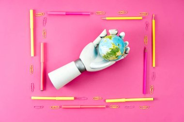 Top view of robotic hand holding earth globe inside of frame made of pencils and markers on pink stock vector