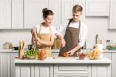 Fotografia coppia cucina insalata e tagliare le verdure in cucina