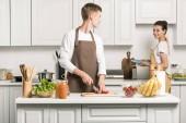přítel, vaření salát a řezání rajčata v kuchyni