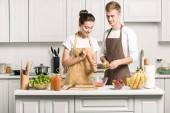 mladý pár vaření salát a přidáním koření v kuchyni