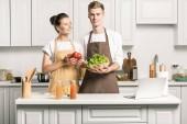 Fotografie mladý pár vaření salát a postavení se zeleninou v kuchyni
