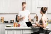 Fotografie Freund mit Glas Milch und Freundin mit Laptop in der Küche