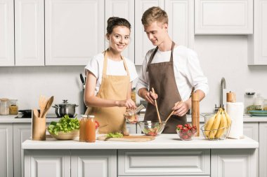 young couple cooking healthy salad in kitchen