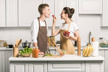 girlfriend feeding boyfriend with strawberry in kitchen
