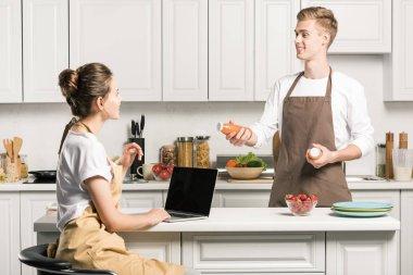girlfriend using laptop, boyfriend holding bottles of juice in kitchen