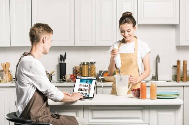 girlfriend cooking and boyfriend using laptop with loaded amazon page in kitchen