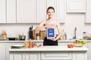 attractive girl holding tablet with loaded facebook page in kitchen