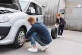 Fotografie Otče měnící pneumatiky v autě kolo klíč, syn drží pneumatiku