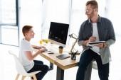 Fotografie otec drží tužku a zápisník, syn doma pomocí počítače