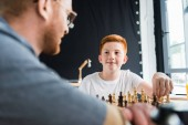 Photo father and son playing chess and looking at each other at home