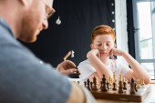 Photo pensive son looking at chessboard at home