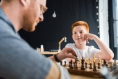Photo son looking at father playing chess at home