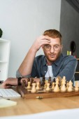 Photo handsome pensive man looking at chessboard at home