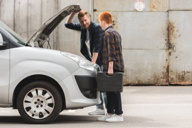 side view of father and son repairing car with open hood on weekend