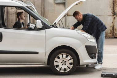 side view of father and son repairing car with open hood