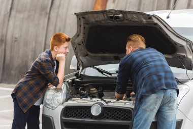 pensive son looking how father repairing car with open hood