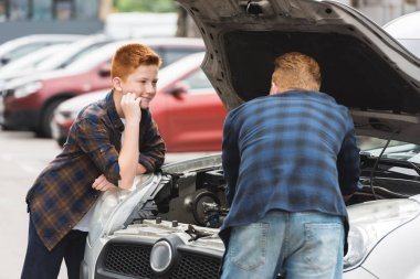 son looking how father repairing car with open hood