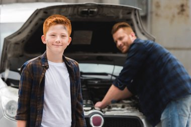 father repairing car with open hood, smiling son looking at camera