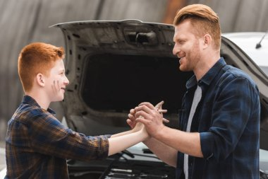 father and son holding hands after repairing car