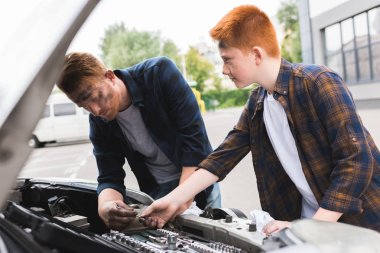 son giving tool for repairing car to father