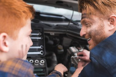 happy father and son repairing car with open hood and looking at each other