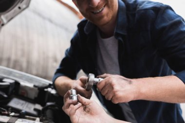cropped image of father and son repairing car with open hood and holding tools