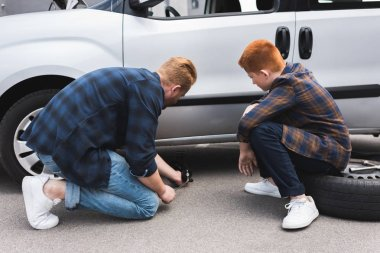father lifting car with floor jack for changing tire, son sitting on tire