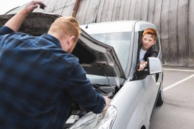 father repairing car with open hood, son sitting at driver seat