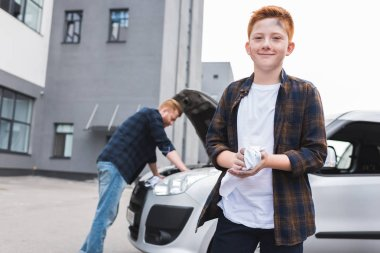 father repairing car with open hood, son looking at camera
