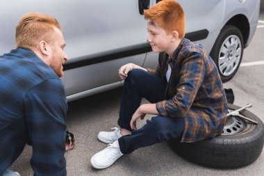 father and son changing tire in car with floor jack and looking at each other