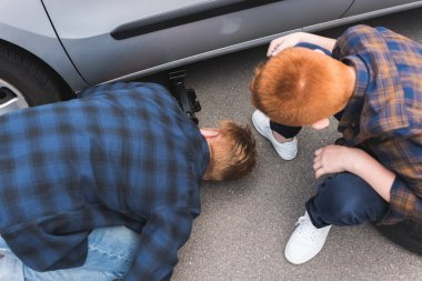 high angle view of father and son lifting car with floor jack for changing tire
