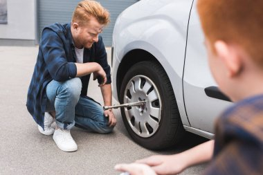 father changing tire in car with wheel wrench, son sitting near