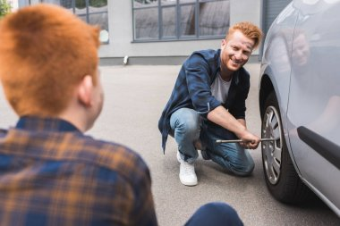 father changing tire in car with wheel wrench and looking at son