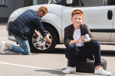 father changing tire in car with wheel wrench, son sitting and looking at camera