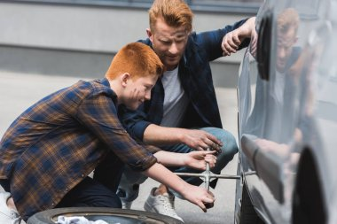 side view of father and son changing tire in car with wheel wrench