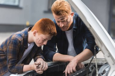 father and son repairing car and looking in open hood
