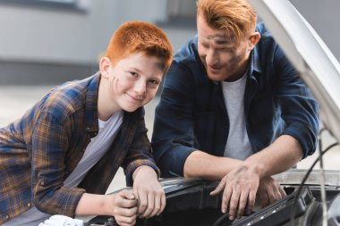 ginger hair father and son repairing car with open hood