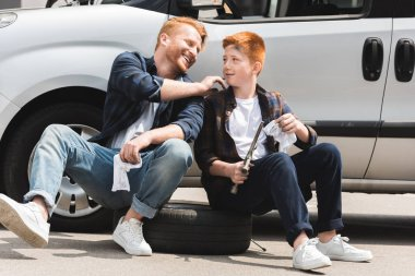 smiling father cleaning son face after repairing car