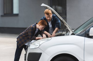 father and son repairing car with open hood