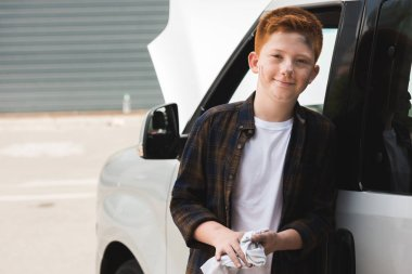 cheerful red hair preteen boy looking at camera after repairing car