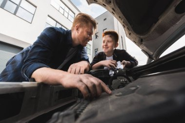 father and son repairing car and looking at each other